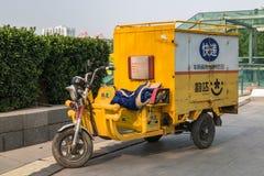 Un motorino o un motobike a tre ruote con una carrozza sulle vie accanto al parco olimpico a Pechino fotografia stock libera da diritti