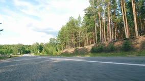 Un motorista en impulsiones del casco en un camino en una moto almacen de metraje de vídeo