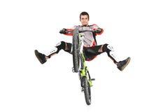 Un motorista joven con su salto de la bici Imagen de archivo