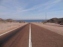 Un motorista monta en el desierto Fotografía de archivo libre de regalías