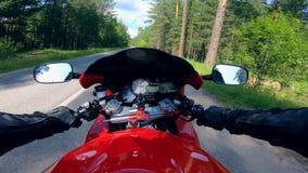 Un motorista que monta una bici roja, sosteniendo las manijas almacen de video