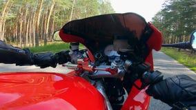 Un motorista que monta una motocicleta, sosteniendo dos manillares almacen de video