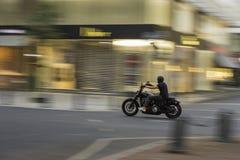Un motorista que se mueve a la velocidad con un efecto de la falta de definición sobre el fondo y sobre el vehículo fotos de archivo