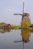 Un moulin à vent à côté d'une maison et arbre dans le kinderdijk avec la belle réflexion de l'eau Image libre de droits
