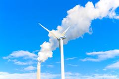 Un moulin à vent électrique et une cheminée d'usine avec de la fumée Images stock