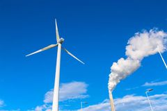Un moulin à vent électrique et une cheminée d'usine avec de la fumée contre le Th Images libres de droits