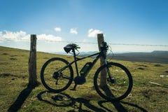 Un mountain bike che riposa su un recinto fotografia stock libera da diritti