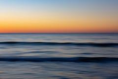 Un mouvement a brouillé le phot de coucher du soleil des vagues et de la lueur d'or de t Photos stock