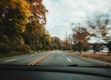 Un mouvement de voiture rapide sur la route avec des arbres images libres de droits