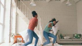 Un movimento lento di due giovani ragazze graziose della corsa mista che saltano sui cuscini di lotta e del letto divertendosi a  stock footage
