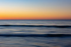 Un movimiento empañó el phot de la puesta del sol de las ondas y del resplandor de oro de t Fotos de archivo