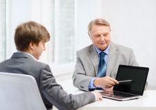 Un más viejo hombre y hombre joven con el ordenador portátil Imagenes de archivo
