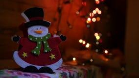 Un muñeco de nieve alegre en un cilindro contra la perspectiva de una guirnalda de luces coloreadas cámara lenta, 1920x1080, hd c metrajes