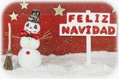 Un muñeco de nieve con un poste indicador con la Feliz Navidad de las palabras en español Imagen de archivo