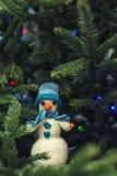 Un muñeco de nieve hecho en casa hecho punto lindo se sienta en las ramas de un Cristo Fotos de archivo