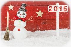 Un muñeco de nieve y un poste indicador con el número 2015 Fotografía de archivo libre de regalías