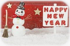 Un muñeco de nieve y un poste indicador con la Feliz Año Nuevo de las palabras Fotografía de archivo libre de regalías