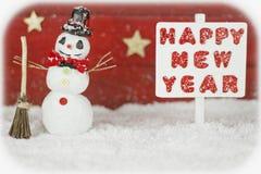 Un muñeco de nieve y un poste indicador con la Feliz Año Nuevo de las palabras Foto de archivo libre de regalías
