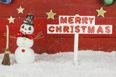 Un muñeco de nieve y un poste indicador con la Feliz Navidad de las palabras Fotos de archivo