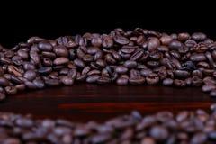 Un mucchio dei chicchi di caffè arrostiti ha accatastato in un cerchio su legno di mogano isolato fotografie stock