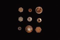 Un mucchio dei dadi, dei bulloni, delle viti e di altri fermi su un fondo nero Immagini Stock Libere da Diritti