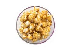 Un mucchio del cereale del caramello in una ciotola su un fondo bianco fotografia stock