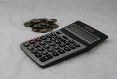 Un mucchio delle monete e del calcolatore tailandesi del bagno sui precedenti bianchi un piano, usato come soldi, calcolatore immagini stock
