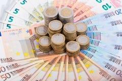 Un mucchio delle monete sulle banconote Fotografia Stock Libera da Diritti