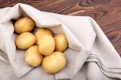Un mucchio delle patate organiche e novelle su un tessuto grigio e su un fondo di legno di marrone scuro Raccolto delle verdure d Fotografia Stock