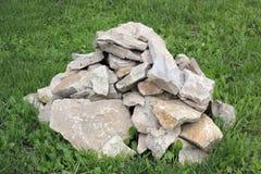 Un mucchio delle rocce ruvide sull'erba verde Fotografia Stock