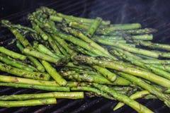 Un mucchio di asparago imburrato spears la torrefazione su una griglia all'aperto con fumo che si stacca di loro immagini stock