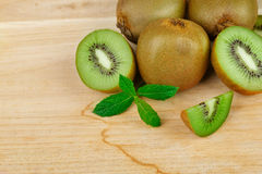 Un mucchio di intero e del taglio sul kiwi maturo dei pezzi e sulla menta fresca su un fondo di legno leggero Vitamine sane ed or Fotografie Stock
