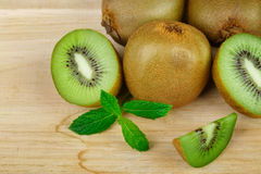 Un mucchio di intero e del taglio sul kiwi maturo dei pezzi e sulla menta fresca su un fondo di legno leggero Vitamine sane ed or Immagine Stock