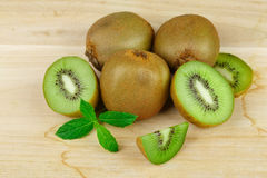 Un mucchio di intero e del taglio sul kiwi maturo dei pezzi e sulla menta fresca su un fondo di legno leggero Vitamine sane ed or Immagini Stock