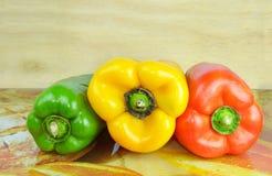 Un mucchio di tre generi differenti di peperoni dolci su un fondo di legno Fotografie Stock