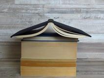 Un mucchio a forma di della casa di vecchi libri sul fondo candeggiato della quercia immagini stock libere da diritti