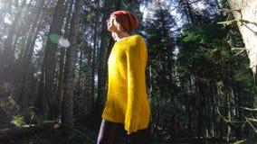 Un muchacha-fotógrafo sano activo del inconformista con una cámara en sus manos camina a través del bosque 60 FPS oscuros lento almacen de video