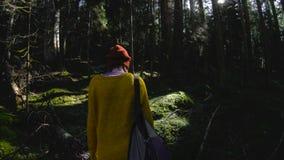 Un muchacha-fotógrafo sano activo del inconformista con una cámara en sus manos camina a través del bosque 60 FPS oscuros lento metrajes
