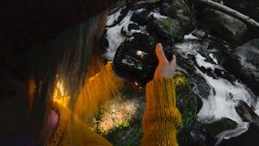 Un muchacha-fotógrafo sano activo del inconformista con una cámara en sus manos camina a través del bosque que la muchacha está m metrajes