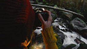 Un muchacha-fotógrafo sano activo del inconformista con una cámara en sus manos camina a través del bosque que la muchacha está t metrajes