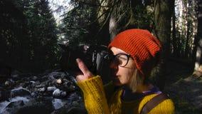 Un muchacha-fotógrafo sano activo del inconformista con una cámara en sus manos camina a través del bosque que la muchacha está t almacen de metraje de vídeo
