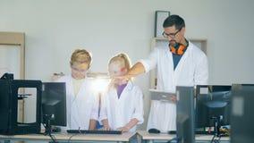 Un muchacho adolescente y una muchacha están mirando un monitor de computadora con un socio de investigación almacen de metraje de vídeo