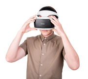 Un muchacho adulto en el casco de la realidad virtual, aislado en un fondo blanco Acción del hombre en gafas de la realidad virtu Imagen de archivo