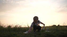 Un muchacho alegre aumenta billetes de dólar de la hierba y los lanza en la cámara lenta almacen de video