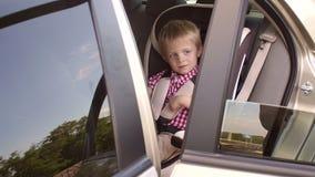 Un muchacho alegre de cinco años en una camisa roja se sienta en un asiento de carro y juegos metrajes
