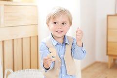 Un muchacho alegre y sonriente lleva a cabo una figura en sus manos Ni?o en guarder?a Retrato del ni?o masculino de moda Posición imagen de archivo
