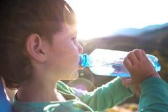 Un muchacho bebe el agua de una botella Foto de archivo libre de regalías