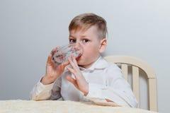 Un muchacho bebe el agua de una taza de cristal fotografía de archivo libre de regalías