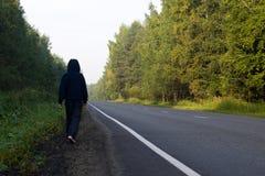 Un muchacho camina a lo largo del borde de la carretera en un bosque hermoso Fotografía de archivo libre de regalías