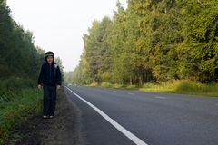Un muchacho camina a lo largo del borde de la carretera en el bosque Foto de archivo